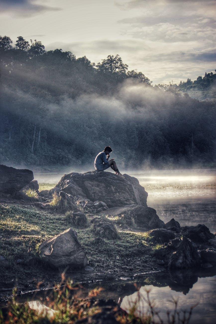 man in gray shit sitting on rock boulder
