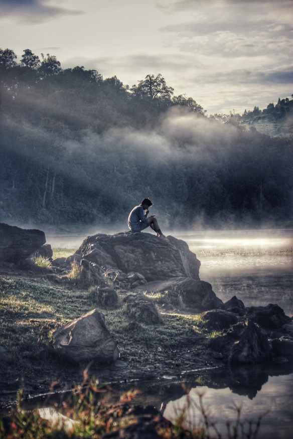 man in gray shit sitting on rock boulder