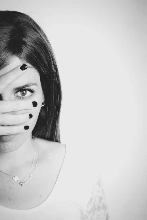 grayscale photo of woman covering her face