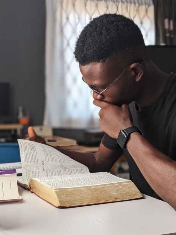 man wearing black crew neck shirt reading book