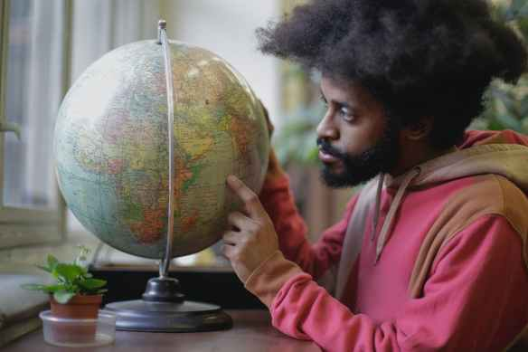 thoughtful young bearded ethnic man with globe sitting at table in modern room